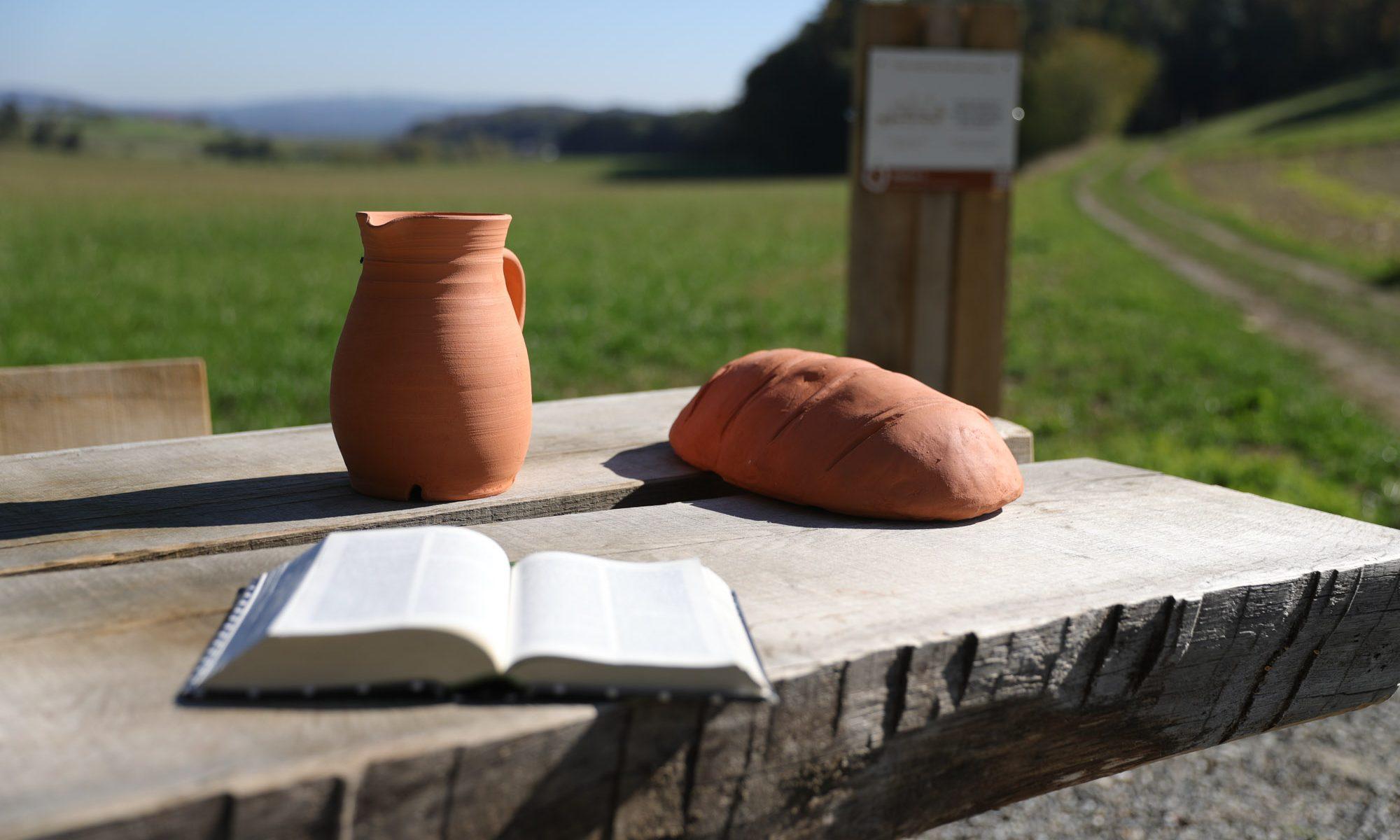 Ein gedeckter Tisch mit Wasser und Brot und einer aufgeschlagenen Bibel an der Station 3 des Vaterunser-Erlebnisweges.