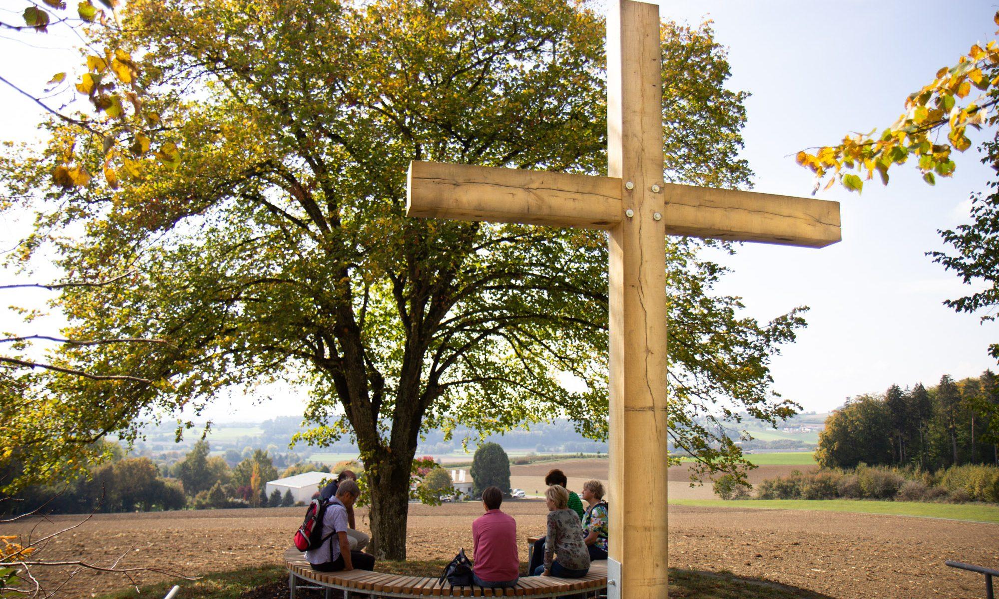 Station 5 des Vaterunser-Weges mit dem Kreuz im Rücken. Davor Menschen auf der Bank.